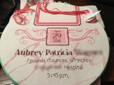 Cross stitched birth sampler